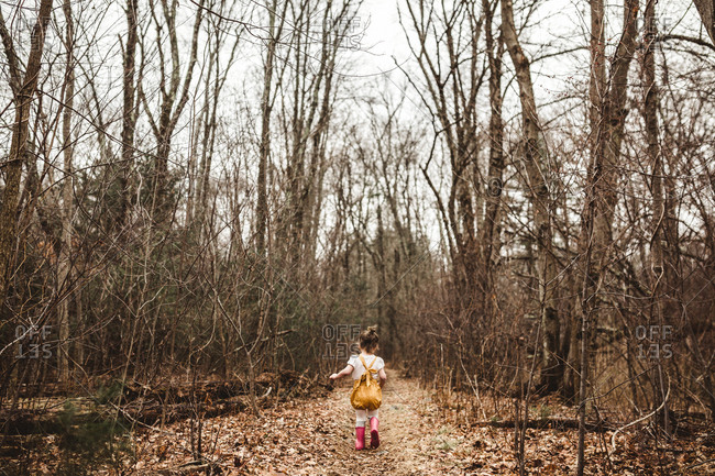 Girl running down wooded trail