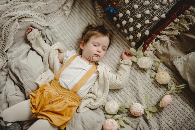 Girl asleep by flower garland