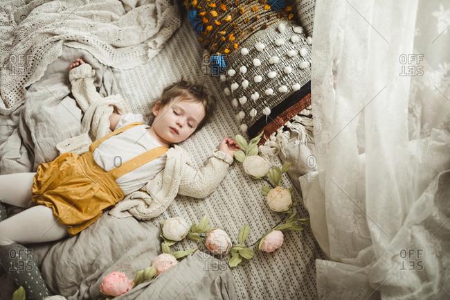 Girl asleep by a flower garland