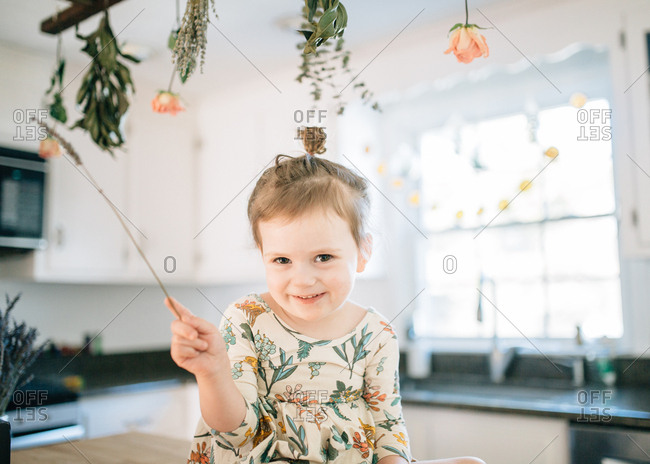 Girl holding lavender sprig in kitchen