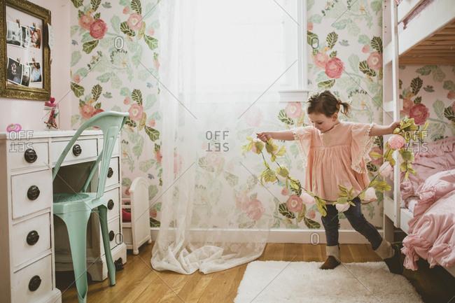 Girl holding flower garland in bedroom