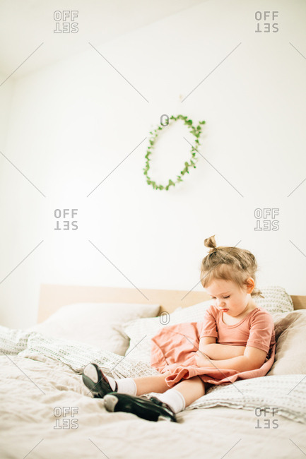 Girl with arms crossed on bed