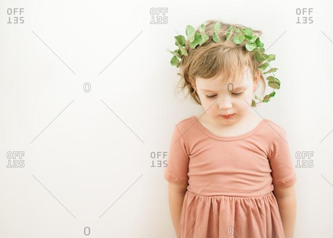 Girl in leaf crown looking down