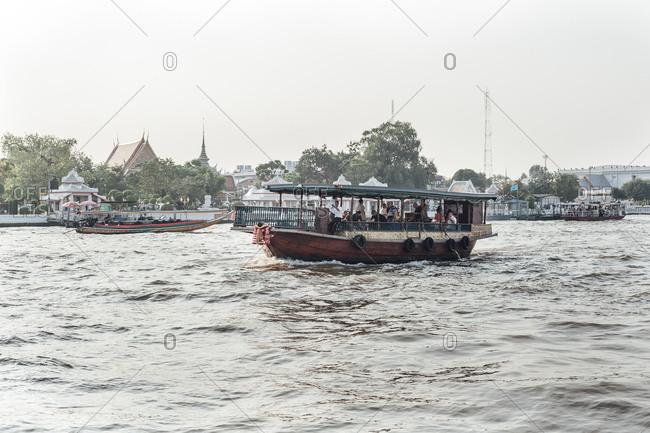 Bangkok, Thailand - November 14, 2010: Boat of tourist crossing the Chao Phraya river