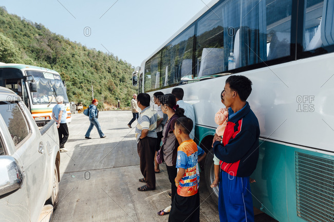 Luang Prabang, Laos - November 20, 2010: Lao citizens watching a tourists bus
