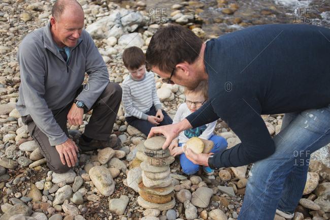 Boys watching men build rock tower