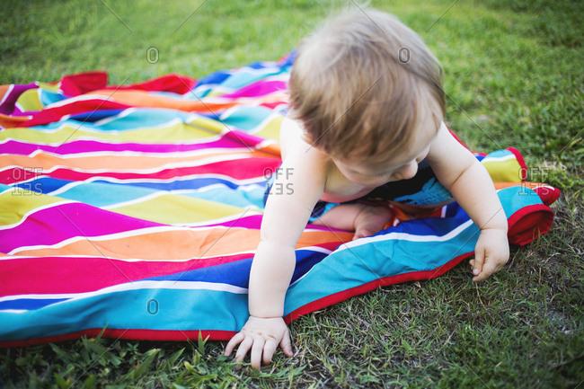 Toddler on blanket picking grass