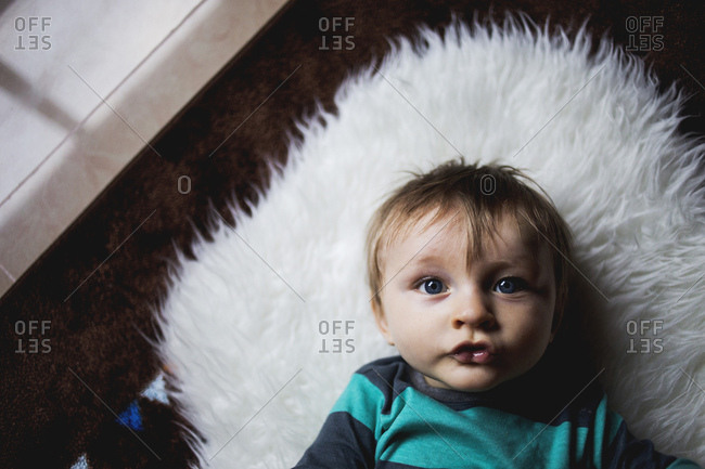 Toddler lying on a fuzzy rug