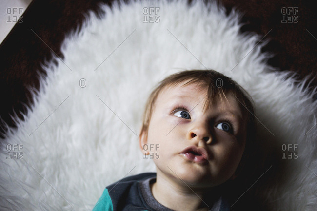 Toddler lying on a furry rug