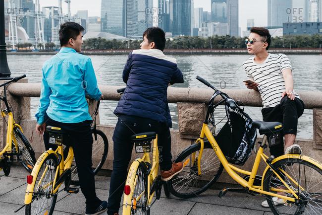 Guangzhou, China - March 26, 2017: young Chinese man using a cell phone on a share bike, in Guangzhou, China.