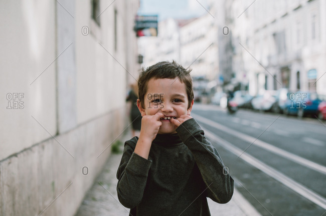 Young boy making a goofy face with his fingers in his mouth