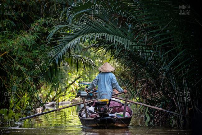 Mekong Delta, Vietnam - January 1, 1904: Vietnamese man rowing a boat in Mekong River