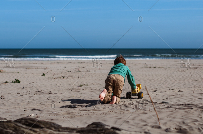 Boy playing with digger alone on the beach