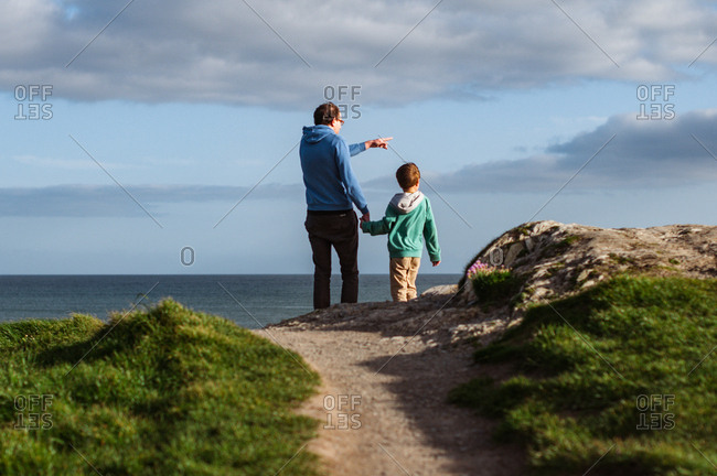 Man holding a boy by hand and pointing to sea on a coastline in Ireland