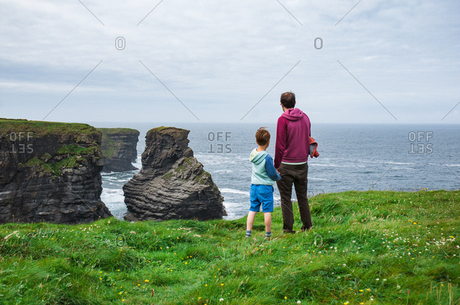 Boy and man standing at the edge of cliffs on the Atlantic coast in county Clare in Ireland