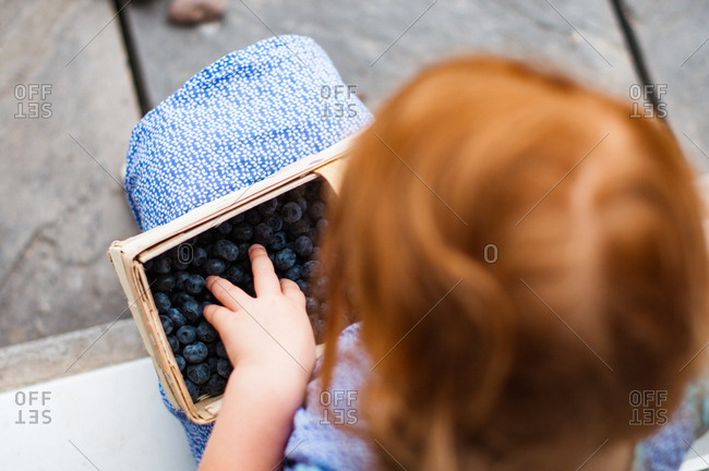 View from above of girl holding a basket of blueberries