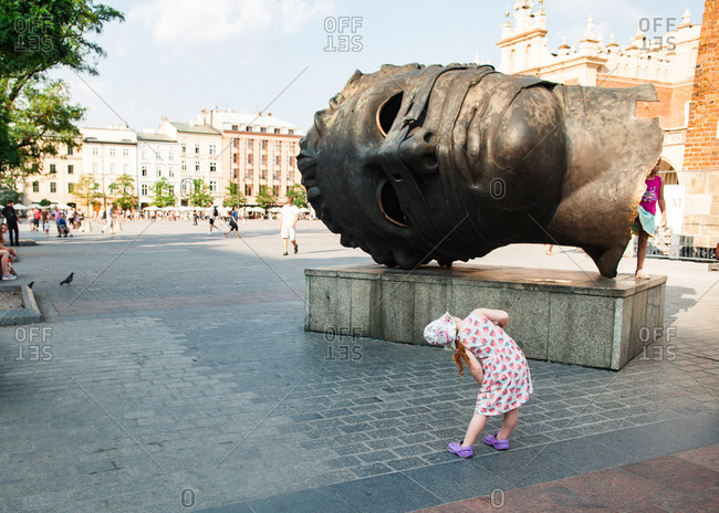 Girl looking at an giant head sculpture on the Main Square in Cracow, Poland