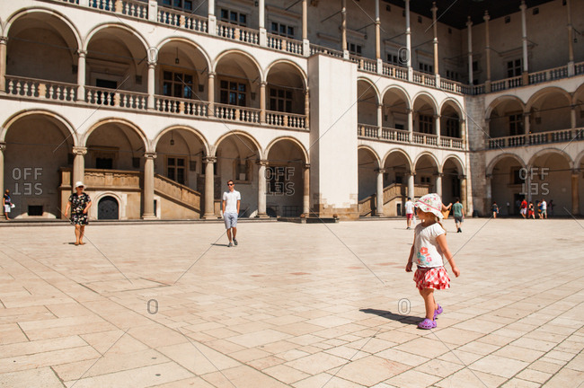 girl looking at the architecture of the Royal Castle in Cracow, Poland