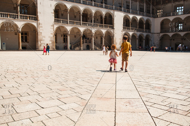 Girl and boy walking at the Royal castle in Cracow, Poland