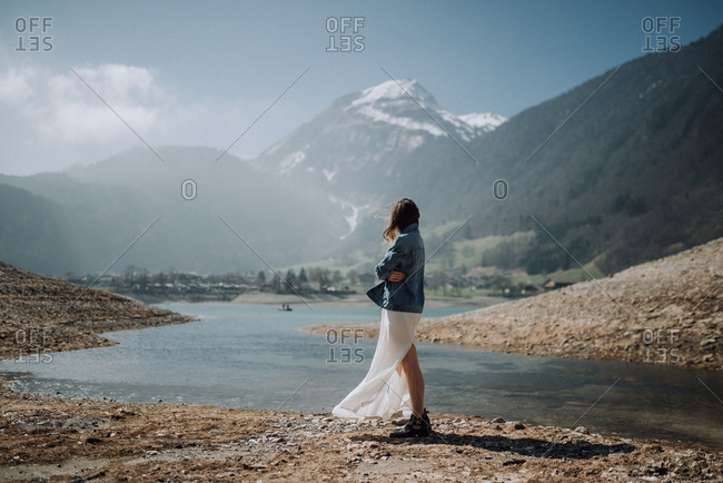 Woman wearing a long white skirt and denim jacket standing along a riverbank looking at mountain scenery