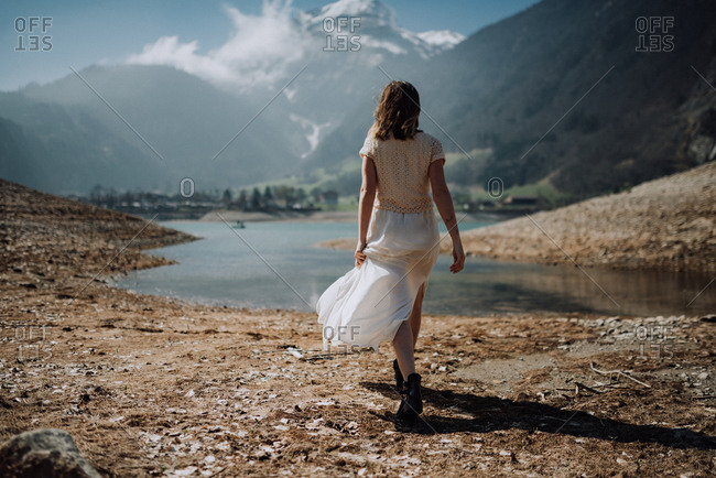 Woman holding her long white skirt walking along a riverbank and looking at mountain scenery