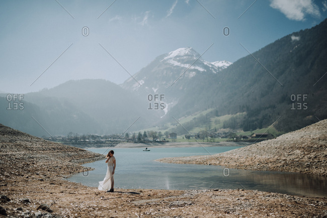 Woman holding her long white skirt standing along the shore of a lake surrounded by steep mountains