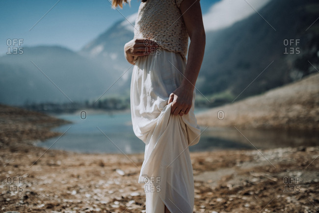 Woman holding her long white skirt standing along a mountain river