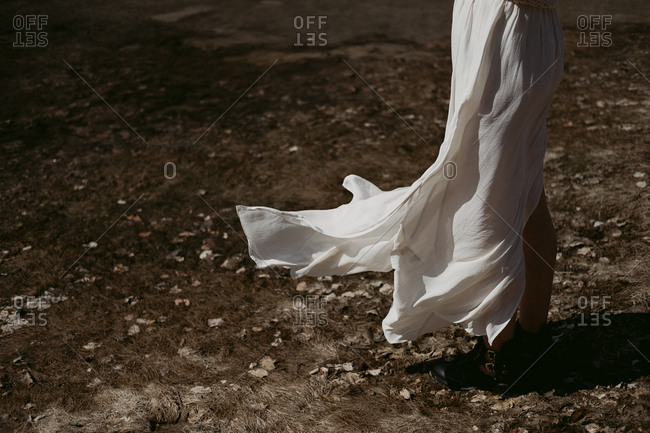 Woman wearing a long white skirt that is flowing in the breeze