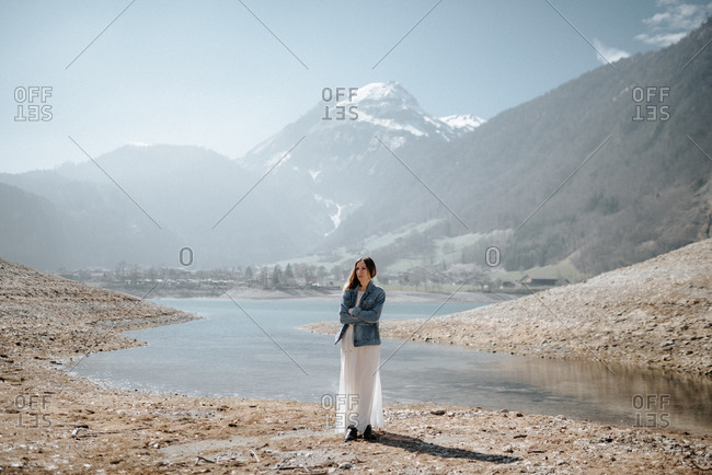 Woman wearing a long white skirt and denim jacket standing along a riverbank surrounded by mountains