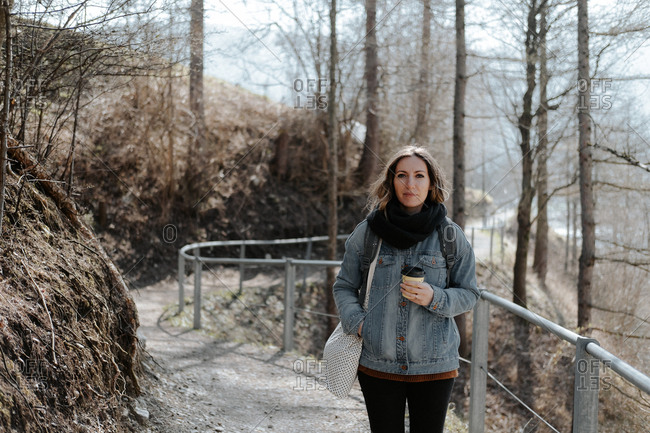 Woman wearing a denim jacket and scarf standing on a nature trail