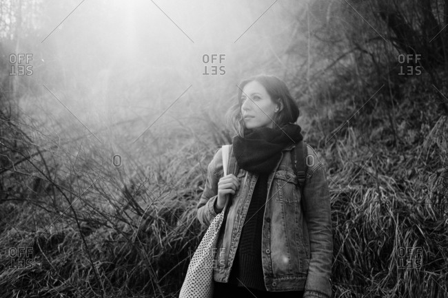 Portrait of a woman wearing a denim jacket and scarf standing outside in nature