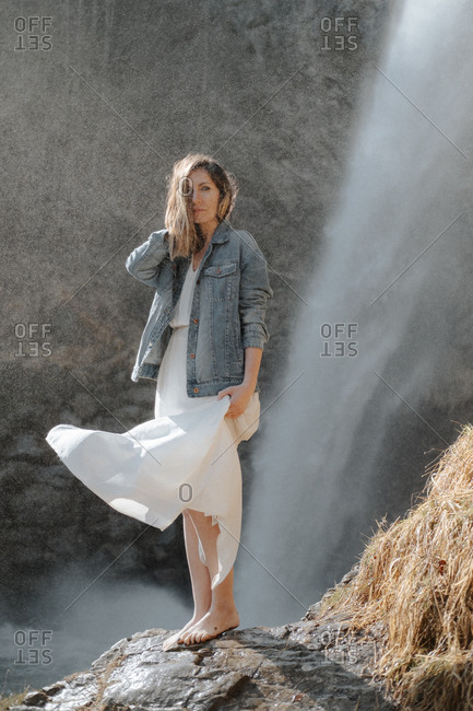 Woman wearing a denim jacket and white dress flowing in the breeze standing barefoot in front of waterfall