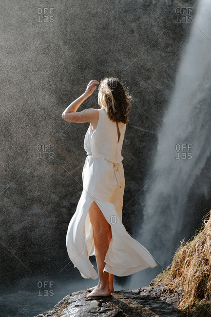 Woman wearing a white dress flowing in the breeze standing barefoot in front of waterfall