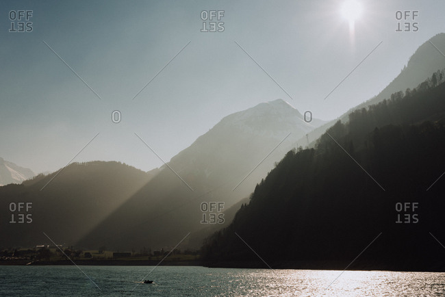 Sun shining on lake surrounded by steep mountains
