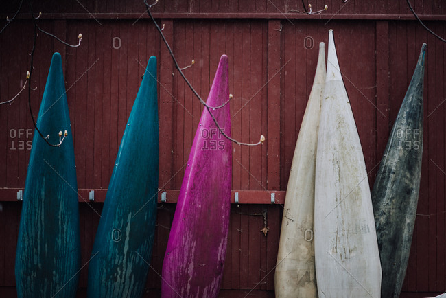 Wooden colored surfboards leaning against fence
