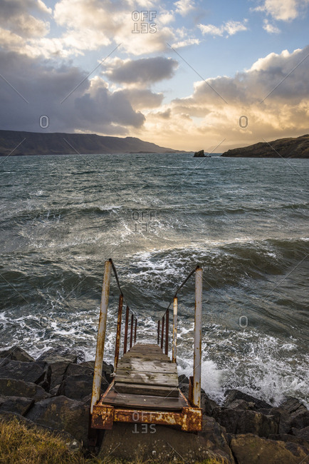 Fierce waves crashing on shore with stairs leading to ocean