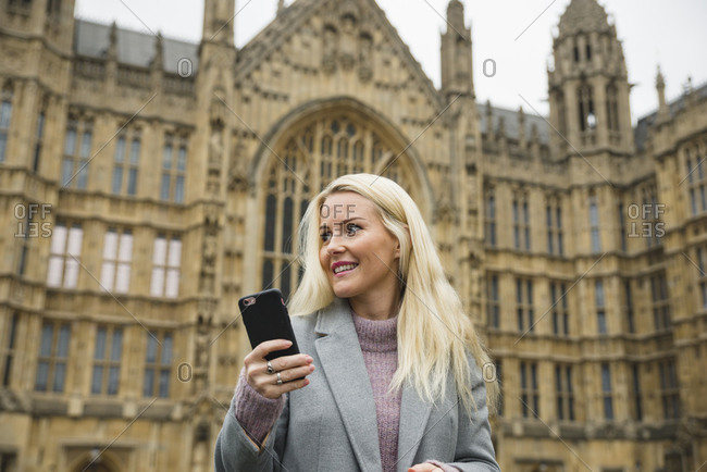 Woman with cell phone in front of the Palace of Westminster