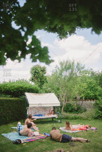 February 4, 2017 - Dordogne, France: People lounging in swimwear in garden