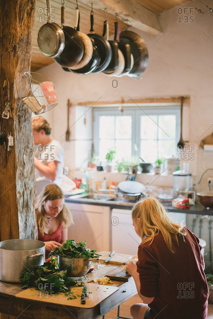 February 4, 2017 - Dordogne, France: Women working at table in cottage kitchen