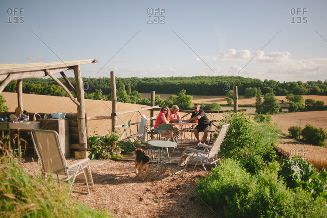February 4, 2017 - Dordogne, France: People sitting around table near outdoor kitchen on farm