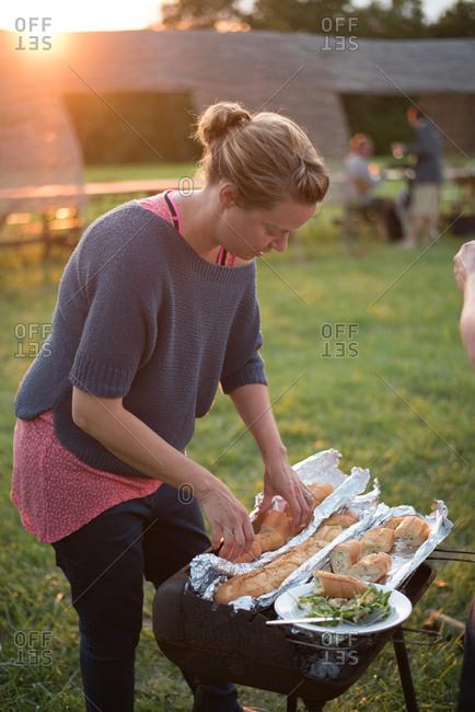 February 4, 2017 - Dordogne, France: Woman preparing bread on grill at dusk