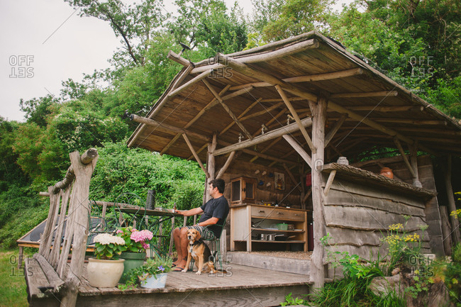 February 4, 2017 - Dordogne, France: Man sitting with dog on porch of camp kitchen
