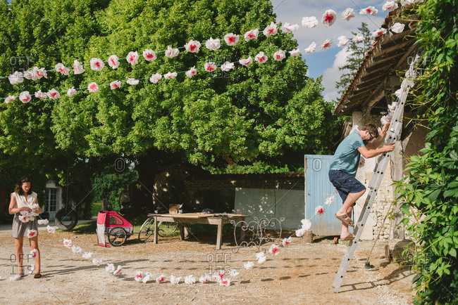 June 30, 2017 - Dordogne, France: People hanging flower garland decorations from roof of building