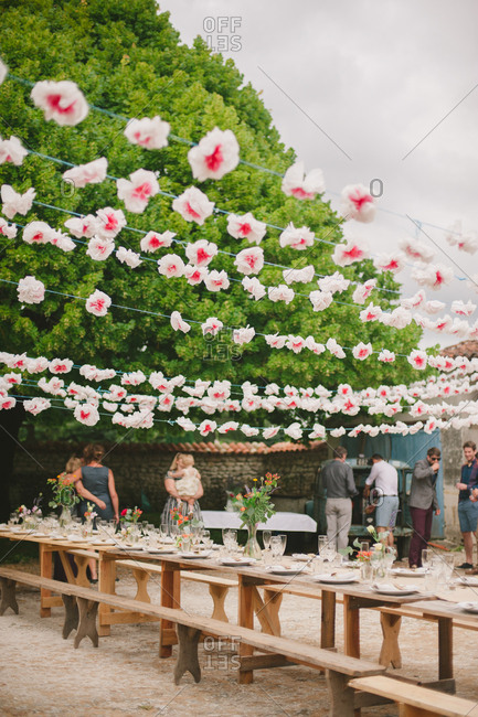 July 1, 2017 - Dordogne, France: Paper flower garlands strung above long dining table set for a party