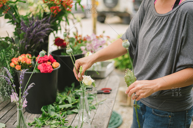Woman arranging flowers outdoors