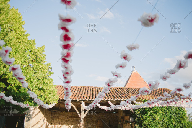 Paper flowers strung up to rustic building