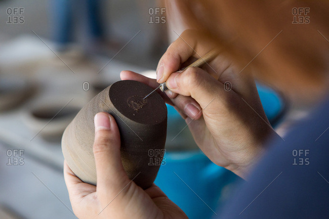 Woman carving into pottery at a ceramic studio in Chiang Mai, Thailand