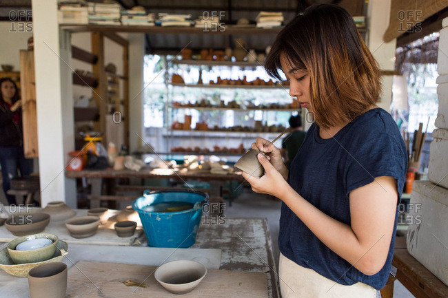 Chiang Mai, Thailand - March 4, 2017: Woman carving into pottery at a ceramic studio in Chiang Mai, Thailand