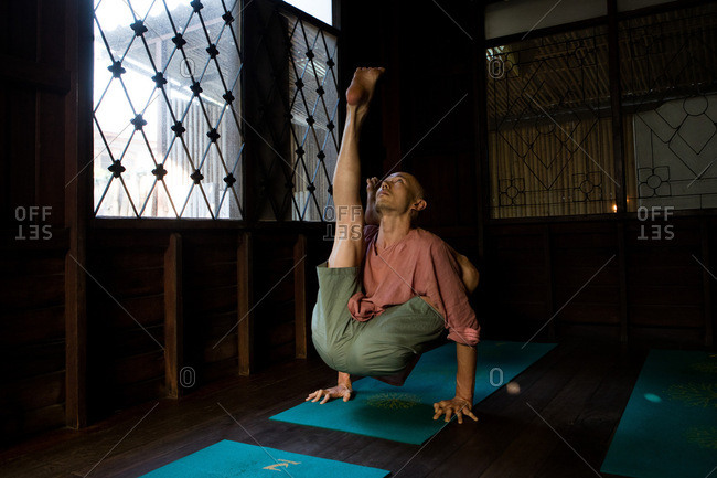Chiang Mai, Thailand - March 5, 2017: Man doing yoga poses in a yoga studio in Chiang Mai, Thailand