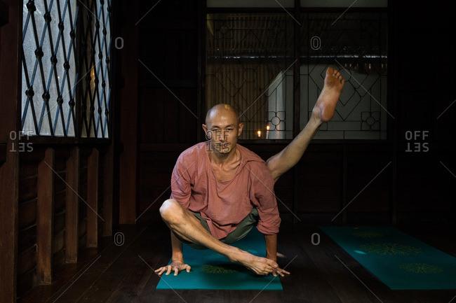 Chiang Mai, Thailand - March 5, 2017: Man practicing yoga in a yoga studio in Chiang Mai, Thailand